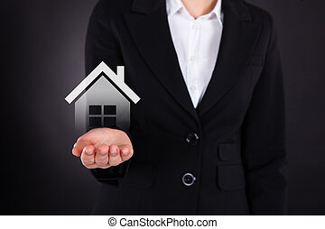 Businesswoman Holding House Model - Midsection of...