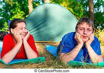 happy couple holding a camping holiday in the park