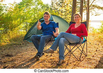 happy and cheerful couple camping on the nature