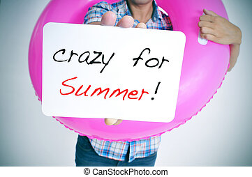 crazy for summer - young man with a pink swim ring showing a...