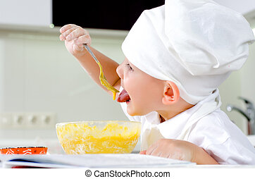 Cute little chef tasting his cooking - Cute little chef in a...