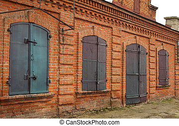 Historical old closed metal windows shutter in brick wall