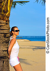 Girl leaning on the palm tree - Girl standing on the beach...