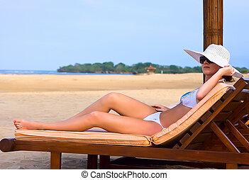 Brunette in white hat on chaise longue - Brunnette girl in...