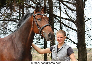 Young blonde woman and bay horse together portrait