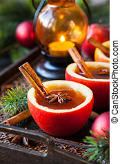 Apple cider with cinnamon sticks and anise star in apple...