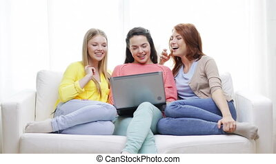 three smiling teenage girls with laptop at home -...