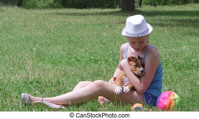 Child holding puppy dog on a grass - Child holding american...