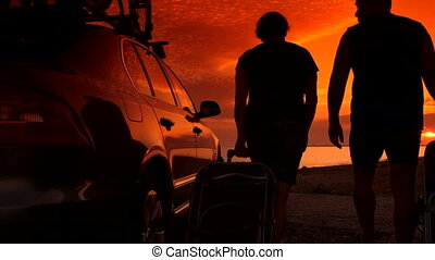Couple with suitcases near his car enjoying sunset at summer beach