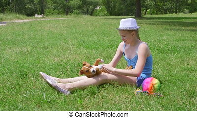 Happy child playing with her puppy dog at grass in summer...