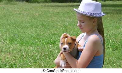 Little girl holding puppy on a grass