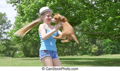 Little girl with her puppy dog spinning on grass in summer...