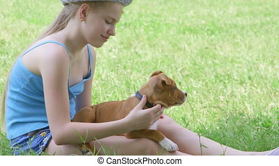 Child with puppy dog on green lawn in summer day - Child...