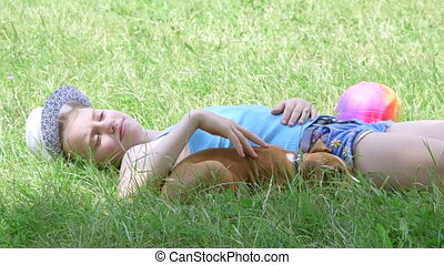 Child with puppy dog relaxing on the grass in summer day