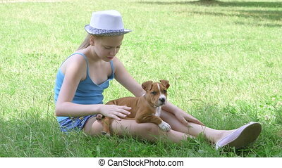 Little girl with puppy on green lawn in summer day