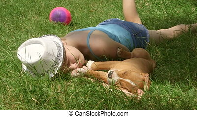 Child with puppy dreaming on grass in summer day