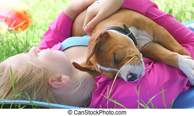 Child with puppy dog dreaming in summer garden