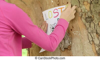 Child posting missing pet poster on tree trunk close-up