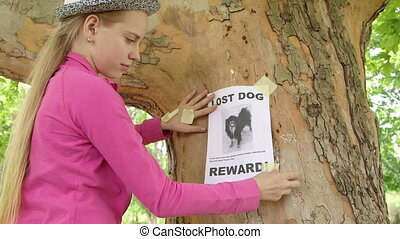 Child posting lost pet sign on on tree trunk - Child posting...