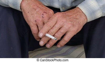 Worn wrinkled hands of senior man with cigarette