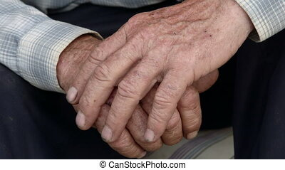 Senior male hands with scraped knuckles and chipped black...