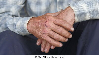 Tired scraped hands of elderly farmer