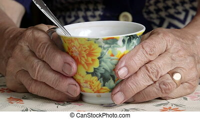 Wrinkled hands of senior woman with cup of drink close-up