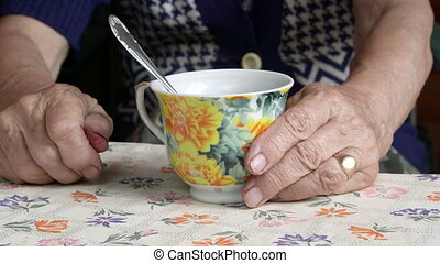 Senior woman hands with a cup of tea closeup