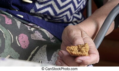 Elderly woman hands with a piece of bread closeup