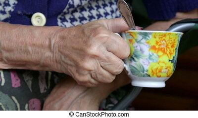 Senior woman hands holding cup of tea closeup