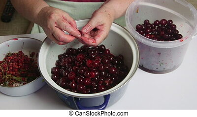 Woman removes the pits from cherries for cooking cherry jam