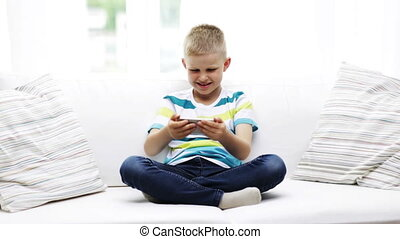 smiling boy playing with smartphone at home - home, leisure,...