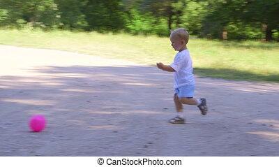 Cute kid runs and kicks the ball