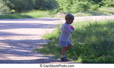 Little boy playing with ball in a summer park