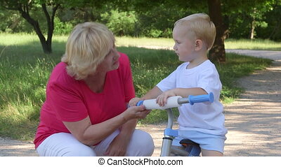 Smiling grandma learning her grandson to ride bicycle in park