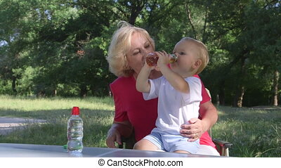 Grandmother with her grandson in the park, child drinking juice