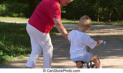 Grandmother assisting grandson to ride a bicycle in the park