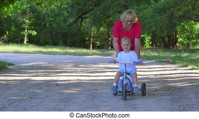 Cheerful child learning to ride a bicycle