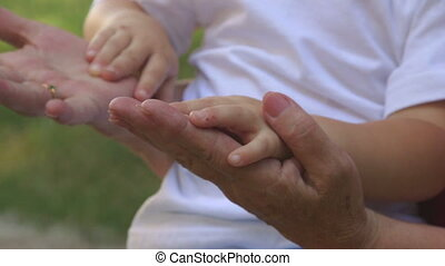 Grandmother and grandson holding hands close-up