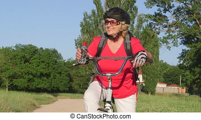 Active senior woman cyclist on bicycle smiling - Active...