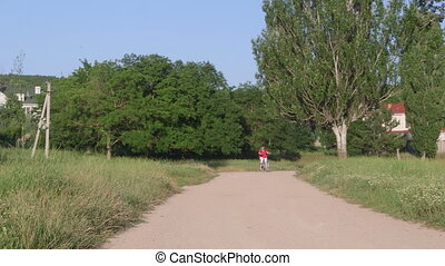 Active senior woman cyclist riding bicycle in the park