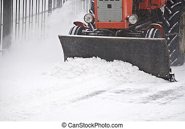 Tractor removes snow - Small tractor clears snow on a city...