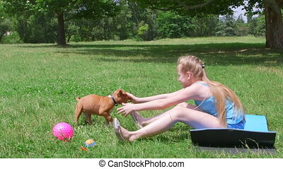 Little girl with a puppy dog having fun on grass in summer park