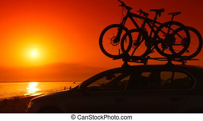 Car with mounted bicycles on summer beach at sunset -...