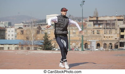 Hip-hop dancer in cap dances in the street of Sarajevo,...