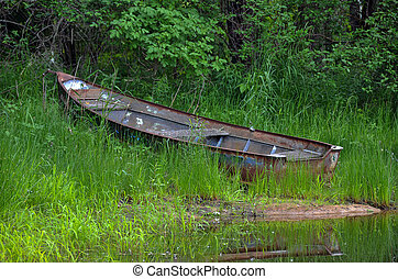 rusty row boat in weeds - Old abandoned row boat in weeds by...