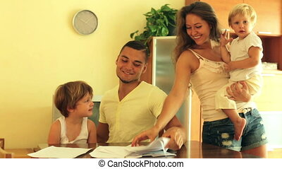 Happy family of four signing document - Young parents with...