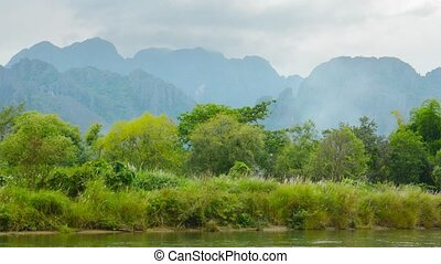 Bank of the river and high mountains in the background. Laos, Vang Vieng