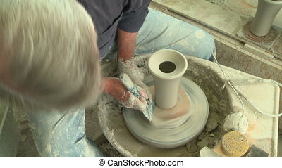 Potter finishes a vase 1 - Potter making a vase on the wheel