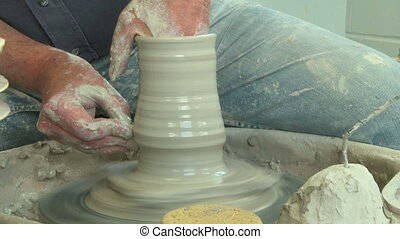 Potter shaping a tall vase 5 - Potter shaping a vase on the...